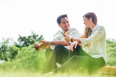 Young Asian lovely couple or college students sit listening to song music on smartphone together in park. Leisure activity, Online love, internet dating app technology, or casual lifestyle concept